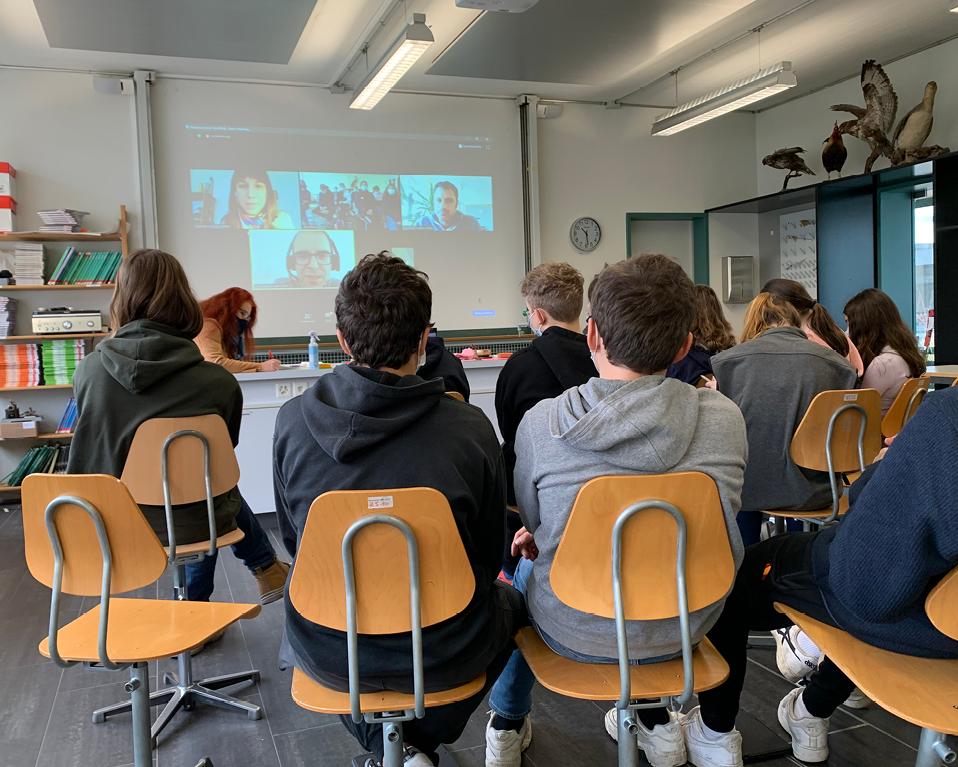 Schulklasse verfolgt Präsentation auf einer Leinwand