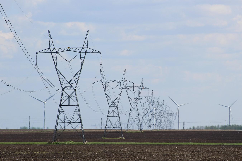 Hochspannungsleitung und Windkraftanlagen im Hintergrund